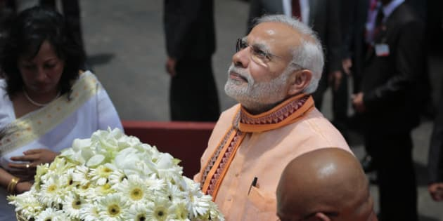 India's Prime Minister Narendra Modi walks with a tray of flowers to offer at Maha Bodhi Buddhist temple during his visit to Colombo, Sri Lanka, Friday, March 13, 2015. Modi started a two-day visit to Sri Lanka on Friday in an effort to regain influence and mend relations that have been strained due to increased Chinese presence in India's neighborhood. (AP Photo/Eranga Jayawardena)