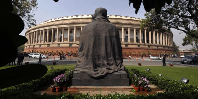 A statue of Mahatma Gandhi overlooks Indian parliament house in New Delhi, India, Saturday, Feb. 28, 2015. India's finance minister announced his government's new budget, promising a slew of measures that attempt to balance welfare spending with high economic growth and infrastructure development while vowing to keep a tight control on fiscal deficit. (AP Photo/ Manish Swarup)