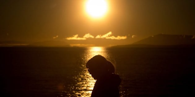 A woman is silhouetted on the deck of the B.C. Ferries vessel Spirit of British Columbia, as the sun rises during a sailing from Tsawwassen, British Columbia, to Swartz Bay on Vancouver Island, on Monday, Nov. 10, 2014. (AP Photo/The Canadian Press, Darryl Dyck)