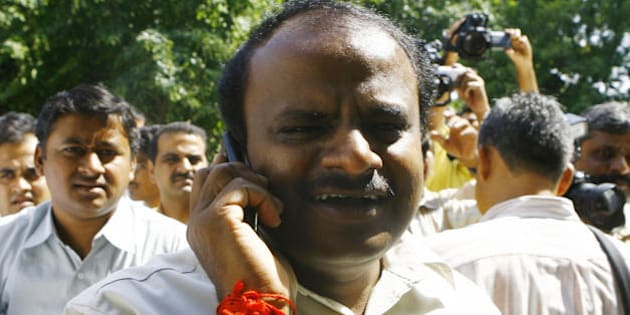 Chief Minister of the Indian state of Karnataka H.D. Kumaraswamy (C) speaks on a cellular telephone while leaving a meeting in New Delhi, 06 October 2007, enroute for Bangalore.  Karnataka is set to witness the collapse of its second coalition government in a span of 20 months and prospects of mid-term assembly polls with the 'betrayed' BJP deciding to withdraw support to the H D Kumaraswamy government after the JDS denied power transfer to it. The abrupt end to the 20-month-old marriage between JDS and BJP after they cobbled up a surprise alliance to rule the state was expected in the wake of escalating strains in their relations and JD(S) sending clear signals that it was not for handing over the baton to the saffron party on October three as agreed earlier.   AFP PHOTO/ Manpreet ROMANA (Photo credit should read MANPREET ROMANA/AFP/Getty Images)