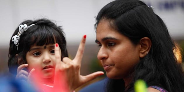 MUMBAI, INDIA - FEBRUARY 7: A woman and a child share light moment near an art installation during the Hindustan Times Kala Ghoda Arts Festival on Day 1, on February 7, 2015 in Mumbai, India. The Hindustan Times Kala Ghoda Arts Festival (KGAF) is one of the most popular cultural fests in Mumbai that draws art lovers from all over the city. Apart from the various art and music attractions at this year's event, a highlight will also be the smoke-free venue. It's an initiative taken by Fortis Healthcare, the official healthcare partner of KGAF 2015. (Photo by Pratham Gokhale/Hindustan Times via Getty Images)