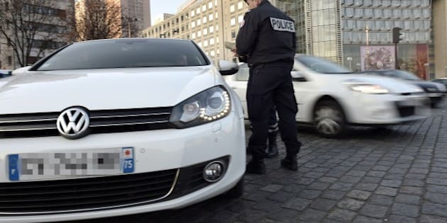 Police officers check the documents of a driver as they enforce pollution control measures in Paris on March 23, 2015.  French authorities put in place emergency traffic-limiting measures in Paris, as the City of Light and much of northern France suffers from a choking smog.City mayor Anne Hidalgo had asked authorities to prevent one in every two cars from taking to the capital's streets and make all public transport temporarily free in a bid to drive down pollution.  AFP PHOTO / LIONEL BONAVENTURE        (Photo credit should read LIONEL BONAVENTURE/AFP/Getty Images)