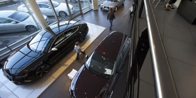 In this photo taken on Tuesday, March  10, 2015, a customer and his son walk to examine a car on a display at an automobile dealership in Moscow, Russia. Russian car sales dropped 37.9 percent year-on-year in February, according to data released Tuesday by the Moscow-based Association of European Businesses, a sharp contrast to steady rises in the rest of Europe. (AP Photo/Alexander Zemlianichenko)