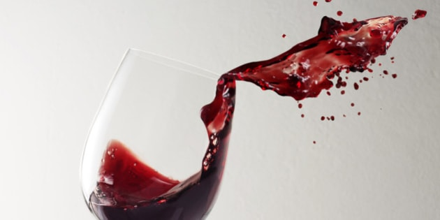 Glass of red wine spilling