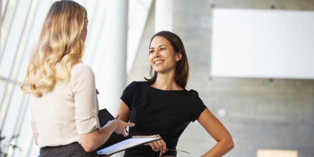 Two Businesswomen Having Informal Meeting In Modern Office Smiling