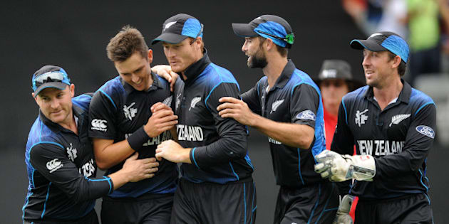 New Zealand's Trent Boult, second left, is congratulated by teammates after dismissing South African batsman Quinton De Kock during their Cricket World Cup semifinal in Auckland, New Zealand, Tuesday, March 24, 2015. (AP Photo/Ross Setford)
