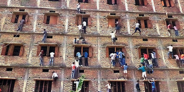 CAPTION CORRECTS THE YEAR - FILE - In this Wednesday, March 18, 2015 file photo, Indians climb the wall of a building to help students appearing in an examination in Hajipur, in the eastern Indian state of Bihar. Education authorities in eastern India say 600 high school students have been expelled after they were found to have cheated on pressure-packed 10th grade examinations. (AP Photo/Press Trust of India, File) INDIA OUT