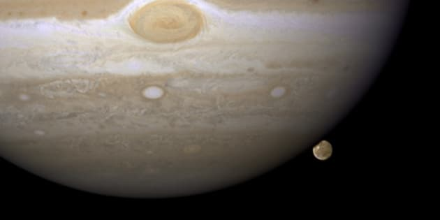 """Hubble Catches Jupiter's Largest Moon Going to the 'Dark Side'  HST/WFPC2 Image of Jupiter and Ganymede Taken April 9, 2007  NASA's Hubble Space Telescope has caught Jupiter's moon Ganymede playing a game of """"peek-a-boo."""" In this crisp Hubble image, Ganymede is shown just before it ducks behind the giant planet.  Ganymede completes an orbit around Jupiter every seven days. Because Ganymede's orbit is tilted nearly edge-on to Earth, it routinely can be seen passing in front of and disappearing behind its giant host, only to reemerge later. Composed of rock and ice, Ganymede is the largest moon in our solar system. It is even larger than the planet Mercury. But Ganymede looks like a dirty snowball next to Jupiter, the largest planet in our solar system. Jupiter is so big that only part of its Southern Hemisphere can be seen in this image.  Hubble's view is so sharp that astronomers can see features on Ganymede's surface, most notably the white impact crater, Tros, and its system of rays, bright streaks of material blasted from the crater. Tros and its ray system are roughly the width of Arizona.  The image also shows Jupiter's Great Red Spot, the large eye-shaped feature at upper left. A storm the size of two Earths, the Great Red Spot has been raging for more than 300 years. Hubble's sharp view of the gas giant planet also reveals the texture of the clouds in the Jovian atmosphere as well as various other storms and vortices.  Astronomers use these images to study Jupiter's upper atmosphere. As Ganymede passes behind the giant planet, it reflects sunlight, which then passes through Jupiter's atmosphere. Imprinted on that light is information about the gas giant's atmosphere, which yields clues about the properties of Jupiter's high-altitude haze above the cloud tops.  This color image was made from three images taken on April 9, 2007, with the Wide Field Planetary Camera 2 in red, green, and blue filters. The image shows Jupiter and Ganymede in close to natural color"""