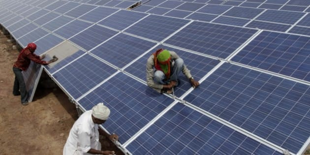 Indian workers install solar panels at the Gujarat Solar Park at Charanka in Patan district, about 250 kilometers (155 miles) from Ahmadabad, India, Saturday, April 14, 2012. Gujarat state Chief Minister Narendra Modi will dedicate the 200 megawatt solar power park, along with other solar projects totaling 600 megawatts of power on April 19. (AP Photo/Ajit Solanki)