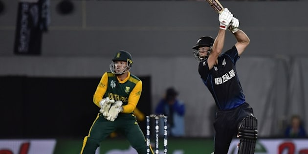 New Zealand batsman Grant Elliott (R) while South African wicketkeeper Quinton de Kock looks on during the Cricket World Cup semi-final match between New Zealand and South Africa at Eden Park in Auckland on March 24, 2015. AFP PHOTO / MARTY MELVILLE        (Photo credit should read Marty Melville/AFP/Getty Images)