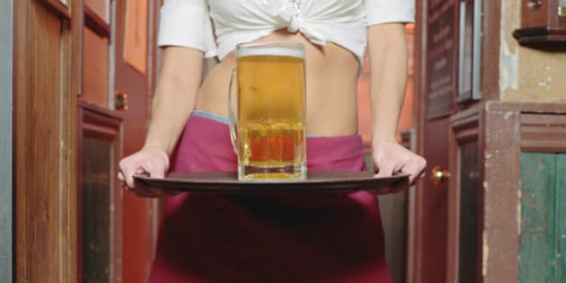 Young waitress holding glass of beer on tray, mid section