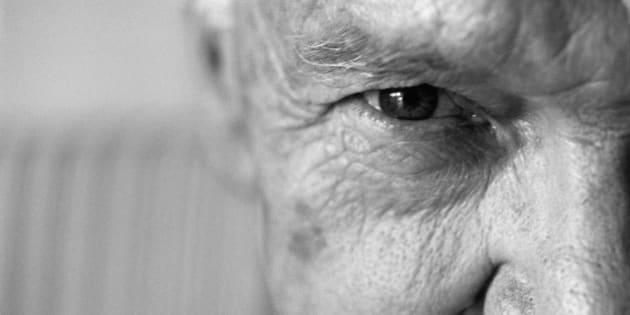 Senior man looking at camera, close-up, cropped