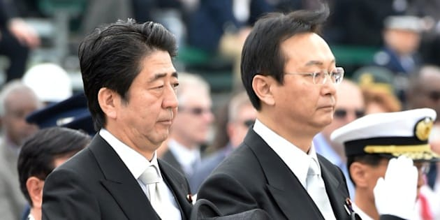 Japanese Prime Minister Shinzo Abe (L) and Defense Minister Akinori Eto (front R) receive the honor guard during a review ceremony at the Japan Air Self-Defense Force's Hyakuri air base at Omitama in Ibaraki prefecture on October 26, 2014. 80 military aircrafts, 25 vehicles and 740 troops participated in the air review. AFP PHOTO / KAZUHIRO NOGI        (Photo credit should read KAZUHIRO NOGI/AFP/Getty Images)