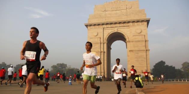 Participants of Delhi Half Marathon run past the India Gate war memorial in New Delhi, India, Sunday, Nov. 23, 2014. (AP Photo/Tsering Topgyal)