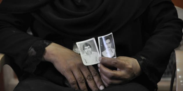 NEW DELHI, INDIA - MARCH 24: A woman shows picture of her relatives who were killed in 1987 Hashimpura massacre during a press conference to express their disappointment at the lower court judgement in the case on March 24, 2015 in New Delhi, India. More than 40 Muslims men were picked up from Hashimpura and killed allegedly by 19 personnel from the Uttar Pradesh Provincial Armed Constabulary (PAC) after riots occurred in parts of Meerut in 1987. All the 16 accused had been set free by a Delhi court on March 21 giving them 'benefit of doubt for want of evidence especially regarding their identity. (Photo by Saumya Khandelwal/Hindustan Times via Getty Images)