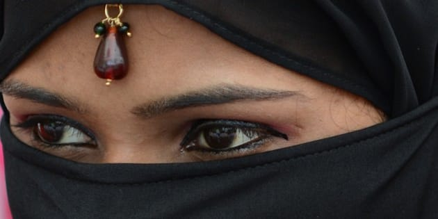 An Indian Muslim bride looks on during a mass wedding ceremony at the ancient Sarkhej Roza mosque and tomb complex in Ahmedabad on March 21, 2015. Some 112 Muslim couples joined the event organised by the Husaini Waqaf Committee. Mass weddings are often welcomed in India for reducing the pressure on parents on organizing and paying for the wedding, with participating couples given basic household items and some jewellery while free food is provided for the couples and their limited invited guests, with the help of generous donors.  AFP PHOTO / Sam PANTHAKY        (Photo credit should read SAM PANTHAKY/AFP/Getty Images)