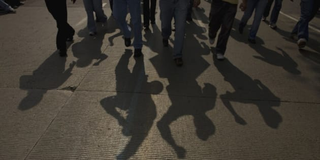 The shadow of electricians is cast on the road as they protest the government's shut down of a state-run power company in Mexico City