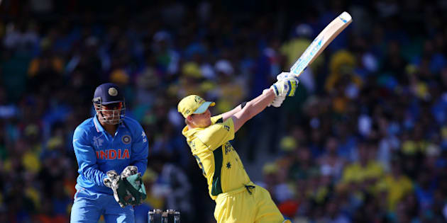 Australia's Steve Smith hits the ball for six runs as India's MS Dhoni watches during their Cricket World Cup semifinal in Sydney, Australia, Thursday, March 26, 2015. (AP Photo/Rick Rycroft)