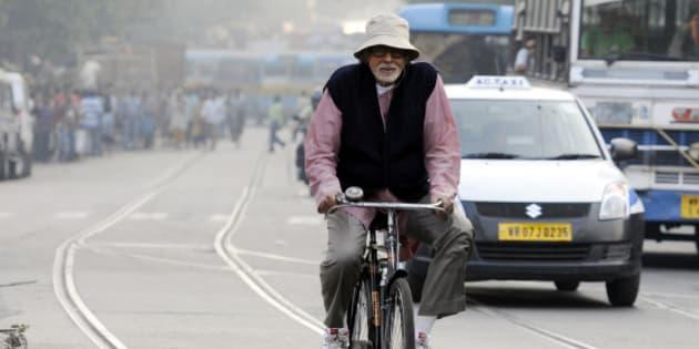 KOLKATA, INDIA - NOVEMBER 6: Bollywood actor Amitabh Bachchan rides a bicycle during shooting for his upcoming film Piku on the roads of Shyambazar on November 6, 2014 in Kolkata, India. (Photo by Subhankar Chakraborty/ Hindustan Times via Getty Images)