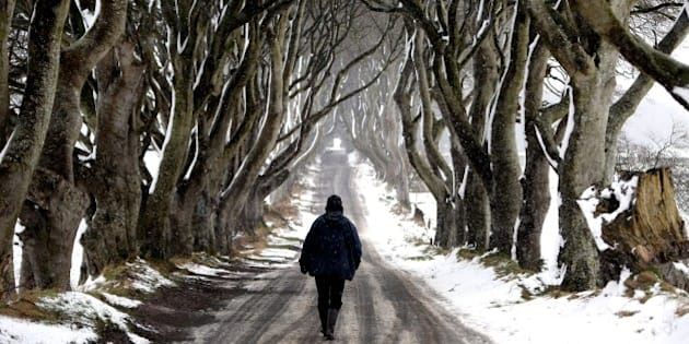 A man walks during snow along the Dark Hedges tree tunnel, which was featured in the TV series Game of Thrones, near Ballymoney in Antrim, Northern Ireland, on January 14, 2015. More than 100 schools and nurseries have been shut and many roads closed as snow and wintry weather swept across the UK. Dozens of schools in Northern Ireland have also been closed because of bad weather.  AFP PHOTO / PAUL FAITH        (Photo credit should read PAUL FAITH/AFP/Getty Images)