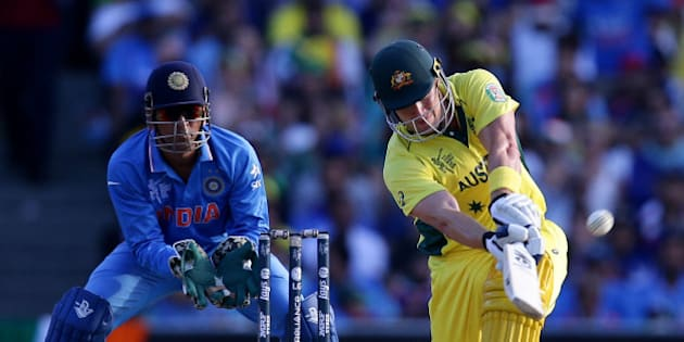 Australia's Shane Watson hits the ball for six runs as India's MS Dhoni watches during their Cricket World Cup semifinal in Sydney, Australia, Thursday, March 26, 2015. (AP Photo/Rob Griffith)