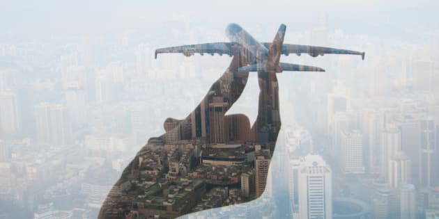 double exposure of mans hand holding a toy plane and cityscape in the background