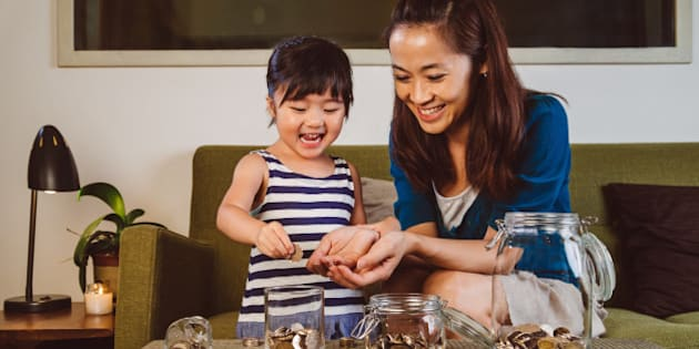 Lovely little girl putting coins into different glass jars on the coffee table joyfully under her pretty young mom's guidance at home.