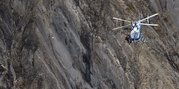 A helicopter carries investigators near scattered debris on the crash site of the Germanwings Airbus A320 that crashed in the French Alps above the southeastern town of Seyne. The young co-pilot of the doomed Germanwings flight that crashed on March 24, appears to have 'deliberately' crashed the plane into the French Alps after locking his captain out of the cockpit, but is not believed to be part of a terrorist plot, French officials said on March 26, 2015. AFP PHOTO / ANNE-CHRISTINE POUJOULAT        (Photo credit should read ANNE-CHRISTINE POUJOULAT/AFP/Getty Images)