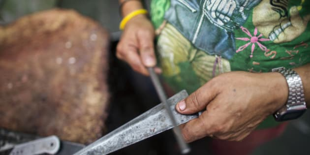 A butcher sharpens a knife before cutting buffalo meat, unseen, at a beef store in New Delhi, India, on Wednesday, March 11, 2015. The government of the state of Maharashtra last week banned possession of beef and its byproducts and the slaughtering of cows, bulls and bullocks. The prohibition marks a victory for hard-line Hindu groups that have sought to protect an animal their religion considers holy. Photographer: Prashanth Vishwanathan/Bloomberg via Getty Images