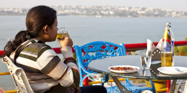 BHOPAL, MADHYA PRADESH, INDIA - FEBRUARY 01: A young Indian woman drinks beer at a terrace with panoramic view of Lake Bhopal on February 1, 2012 in Bhopal, Madhya Pradesh, India  (Photo by EyesWideOpen/Getty Images)