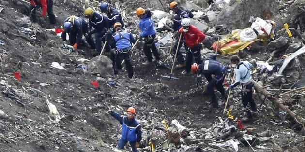 "Rescue workers work on debris of the Germanwings jet at the crash site near Seyne-les-Alpes, France, Thursday, March 26, 2015. The co-pilot of the Germanwings jet barricaded himself in the cockpit and ""intentionally"" rammed the plane full speed into the French Alps, ignoring the captain's frantic pounding on the cockpit door and the screams of terror from passengers, a prosecutor said Thursday. In a split second, he killed all 150 people aboard the plane. (AP Photo/Laurent Cipriani)"