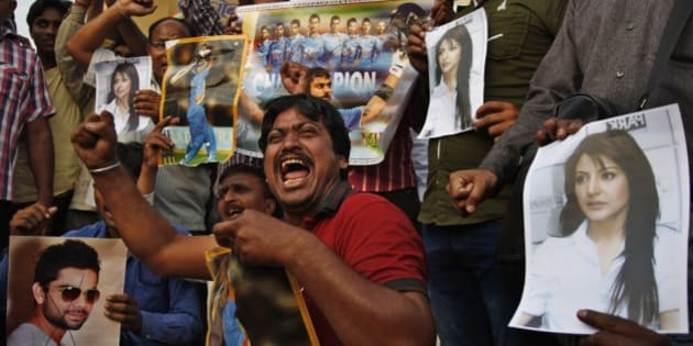 Indian fans shout slogans with posters of  Indian cricket player Virat Kohli, left and his girlfriend and Bollywood actor Anushka Sharma, right, as they react to India's defeat in the ICC cricket world cup semi-final match against Australia, in Ahmadabad, India, Thursday, March 26, 2015. Australia ended 2011 champion India's unbeaten run at the World Cup with a 95-run victory Thursday that ensured the tournament co-hosts will meet in the final. (AP Photo/Ajit Solanki)