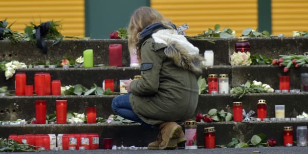 A student kneels down at candles placed in front of the Joseph-Koenig Gymnasium in Haltern, western Germany, Wednesday, March 25, 2015, the day after 16 school children and 2 teachers died in the Germanwings jet airliner crash in the French Alps from Barcelona to Duesseldorf. (AP Photo/Martin Meissner)