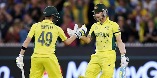 Australian captain Michael Clarke, right, is congratulated by teammate Steve Smith after scoring 50 runs while batting against New Zealand during the Cricket World Cup final in Melbourne, Australia, Sunday, March 29, 2015. (AP Photo/Rick Rycroft)