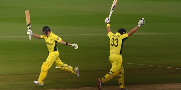 Australia's Shane Watson, right, and Steve Smith raise their bats and take the final run for their seven wicket win over New Zealand in the Cricket World Cup final in Melbourne, Australia, Sunday, March 29, 2015. (AP Photo/Andy Brownbill)