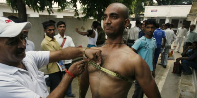 A candidate gets his chest measured as part of a fitness test during recruitment for Uttar Pradesh state police in Allahabad, India, Thursday, Nov. 12, 2009. The state wide recruitment process to fill 35,000 police constable posts started Thursday. (AP Photo/Rajesh Kumar Singh)