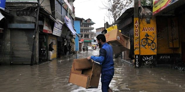 SRINAGAR, INDIA - MARCH 29: Shopkeepers shift merchandise to safer places in wake of accumulation of water in the streets and market places during rain on March 29, 2015 in Srinagar, India. Intermittent rainfall across Kashmir raised water level of streams and rivers, triggering panic among resident of floods. The valley has been witnessing heavy rainfall since Saturday, leading to a sudden surge in water level in rivers, streams and rivulets. The Met Department has predicted more rain over the next six days with heavy rain expected today and on April 3. (Photo by Waseem Andrabi/Hindustan Times via Getty Images)