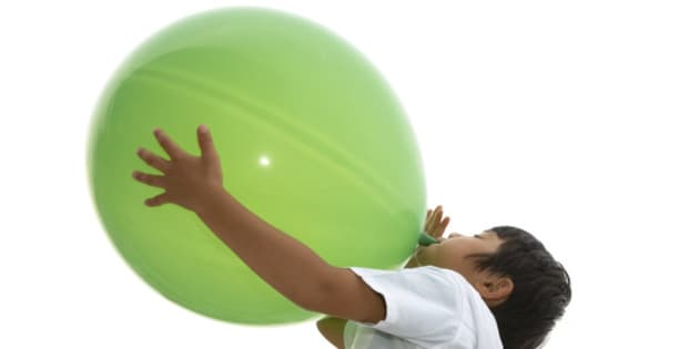 boy blowing up a big green balloon