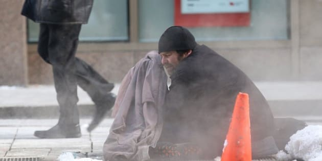 TORONTO, ON - FEBRUARY 23:   A homeless man sits on a city grate to keep himself warm wearing only a jacket in the frigid temperatures.        (Vince Talotta/Toronto Star via Getty Images)