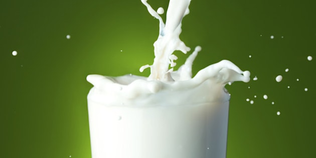 Close-up of a glass with milk that splashing on green background