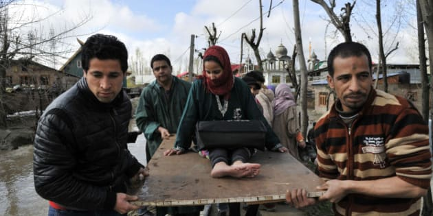 SRINAGAR, INDIA - MARCH 30: Kashmiri men assist a patient woman during evacuation from a flooded area on March 30, 2015 in Srinagar, India. With Jammu and Kashmir facing flood again after the devastating calamity last September, Armed forces have launched a rescue operation by deploying 20 columns in the state and kept helicopters on standby. (Photo by Waseem Andrabi/Hindustan Times via Getty Images)