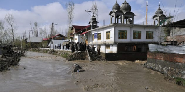 SRINAGAR, INDIA - MARCH 30: Residents look on as a bank of stream is breached by rising flood water on March 30, 2015 in Srinagar, India. With Jammu and Kashmir facing flood again after the devastating calamity last September, Armed forces have launched a rescue operation by deploying 20 columns in the state and kept helicopters on standby. (Photo by Waseem Andrabi/Hindustan Times via Getty Images)