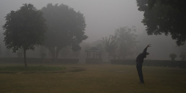 An Indian man exercises in a park on a cold foggy morning in New Delhi, India, Wednesday, Dec. 24, 2014. Cold wave conditions continues unabated in the northern region with fog enveloping most areas and affecting transport services. (AP Photo/Saurabh Das)