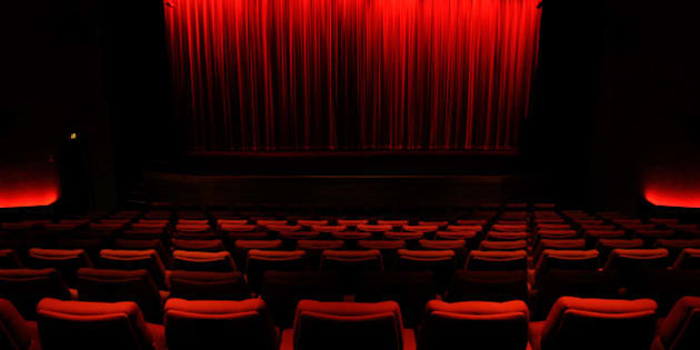 Darkened, empty cinema auditorium with red curtain covering screen, and red chairs.