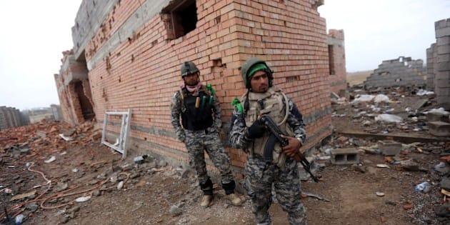 Iraqi security forces stand next a damaged house in the southern entrance of the city of Tikrit on March 29, 2015 during a military operation to retake the northern Iraqi city from Islamic State (IS) group jihadists. IS spearheaded a sweeping offensive last June that overran much of Iraq's Sunni Arab heartland, and the operation to retake Tikrit is Baghdad's largest to date against the militants. AFP PHOTO / AHMAD AL-RUBAYE        (Photo credit should read AHMAD AL-RUBAYE/AFP/Getty Images)