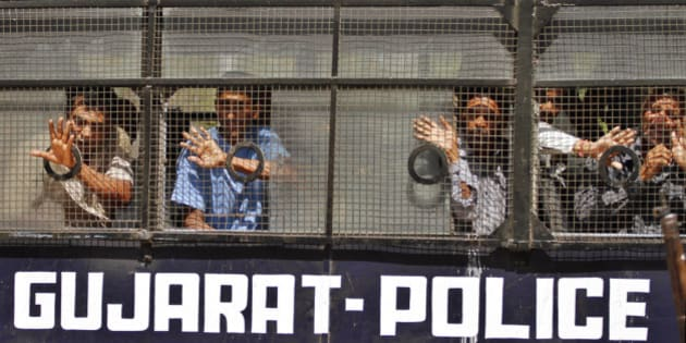 Convicted Indians wave to their families from inside a police vehicle as they are taken away after the pronouncement of sentence at a district court in Anand, about 75 kilometer (47 miles) from Ahmedabad, India, Thursday, April 12, 2012. A court in India has sentenced 18 Hindus to life imprisonment for killing 23 Muslims during religious riots in western India a decade ago. More than 1,000 people, mostly Muslims, died in communal violence that erupted in Gujarat after 60 Hindus were killed in a train fire. The Gujarat riots were one of the worst outbreaks of religious violence in India in the past few decades. (AP Photo/Ajit Solanki)