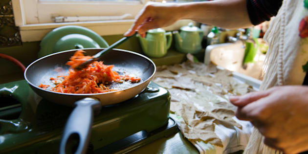 Frying pan on old fashioned gas stove, with carrots and rice. Woman is stirring the ingredients. Wine leaves are drying on a dishtowel on the sink.