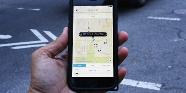 An UBER application is shown as cars drive by in Washington, DC on March 25, 2015. Uber said it was ramping up safety in response to rape allegations against a driver in India and growing concerns about background checks for operators of the popular ride-sharing service. In other cities where Uber operates, critics had complained that a lack of licensing and background checks of drivers could imperil those who use the service. AFP PHOTO/ ANDREW CABALLERO-REYNOLDS        (Photo credit should read Andrew Caballero-Reynolds/AFP/Getty Images)