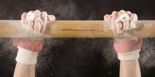 Hands of gymnast hanging on bar