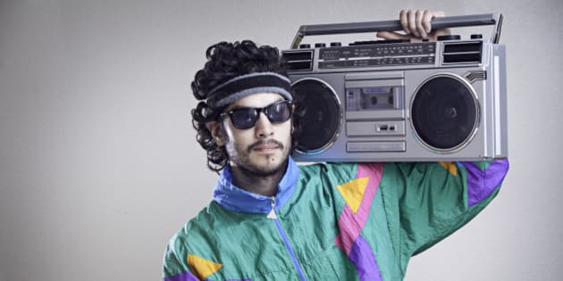 A cool, funky young hipster adult from the late 20th century complete with mullet, boom box 'ghetto blaster' stereo, fluorescent track suit, and tinted sun glasses.  Horizontal with copy space.